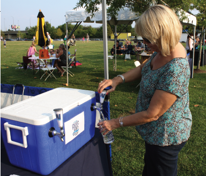 A customer fills a reusable bottle with Louisville pure tap® at a Waterfront Park fill station, units set up for special events and provides an ongoing supply of chilled water.