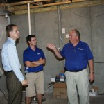 At an energy-efficient home in the Blackford Oaks Subdivision, builder James Monroe, left, speaks with Roy Honnican of Bluegrass Energy, right, about the home's geothermal HVAC system.