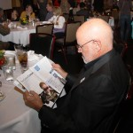 A Rising Stars dinner attendee reads BG Lexington, a young professionals magazine produced by The Lane Report.