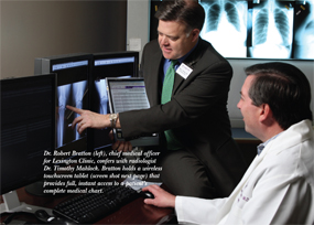 Dr. Robert Bratton, chief medical officer for Lexington Clinic, confers with radiologist Dr. Timothy Mahlock. Bratton holds a wireless touchscreen tablet that provides full, instant access to a patient's complete medical chart.