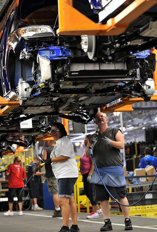 Workers at Ford's Louisville Assembly Plant assemble the all-new Escape in this June 2012 file photo, after an employee celebration to mark the  transformation of the facility. (Photo by Sam VarnHagen/Ford Motor Co.)