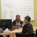 ReGina Beneford, behind the desk, and Trilby Gustafson, work at the Amazon call center in Winchester.