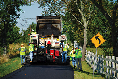 A road construction crew paves a scenic Kentucky roadway with asphalt. The Kentucky Transportation Cabinet invests in hundreds of paving projects each year.