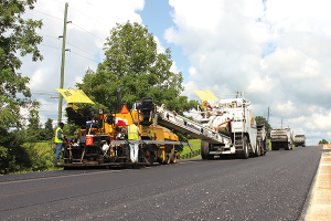 Asphalt is laid down in layers and then compacted by a Kentucky road paving crew. The asphalt industry touts its product as versatile and built to last.