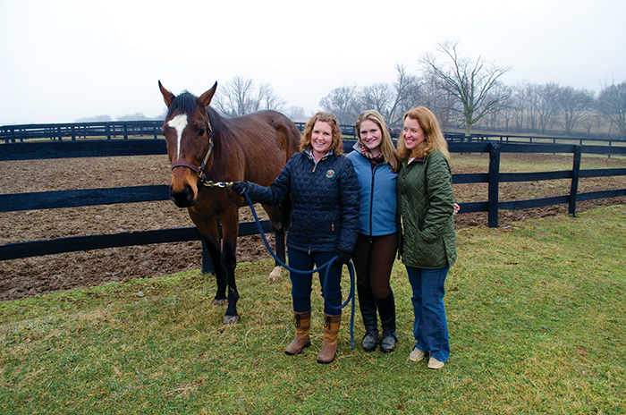 From left, Leslie Pratt, Rachel Meffert and Kim Smith interact with retired racehorse, Where U At, at Moserwood Farms in Prospect, Ky.