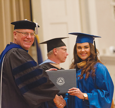 Dean David Blackwell of the University of Kentucky Gatton College of Business and Economic awards an MBA degree.