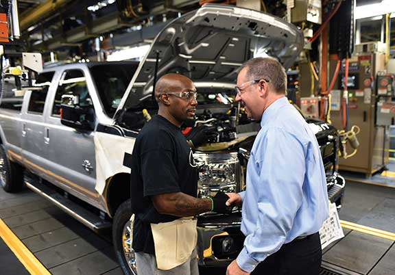Joe Hinrichs, right, president of The Americas, Ford Motor Co., tours the assembly line in December 2015 and speaks with team member LaDrell Whitehead before announcing that a $1.3 billion investment is bringing 2,000 new jobs to Kentucky Truck Plant in Louisville.