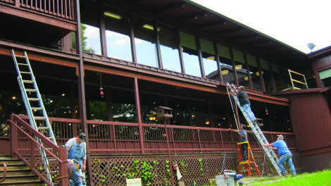 Workers paint the exterior of the Carter Caves State Resort Park lodge as part of the Kentucky State Parks system's Refresh The Finest update program.
