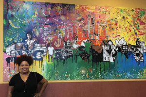 Artist Ashley Cathey with her mural at the Kroger location on Broadway in Louisville.
