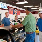 James and Jean Beattie, behind the counter, talk with Dwayne McKinney and Greg Drake, Butler County agriculture and natural resources extension agent, during the grand opening of their businesses in Morgantown.