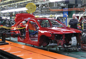 Toyota team members assemble a vehicle March 18 in Georgetown at Toyota Motor Manufacturing Kentucky. The worker inside the vehicle is sitting on a device Kentucky team members suggested for easier access to their task.