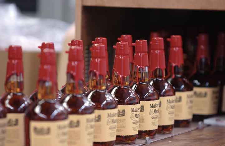 Maker'€™s Mark bottles are transported down an assembly line at the distillery in Loretto, Ky.