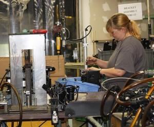 A worker assembles compressor parts at Hitachi Automotive Systems in Berea, Ky.
