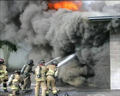 Lexington fire crews operate at a commercial building fire with heavy smoke and flames.