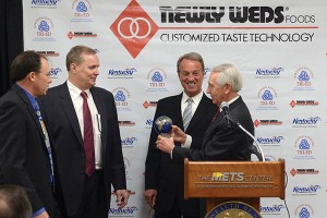 Leo Culligan, vice president of purchasing for Newly Weds Foods, and Mike Hopp, vice president of manufacturing, present Northern Kentucky Tri-ED Chair/Boone County Judge Executive Gary Moore and Gov. Steve Beshear with a gift showcasing the company's global presence.