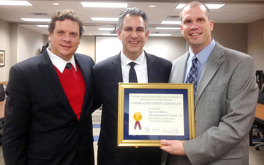 Superior Battery's Juan Sierra, left, and Ray Goodearl, right, accept the Export Achievement Certificate from International Trade Undersecretary Francisco J. Sánchez.