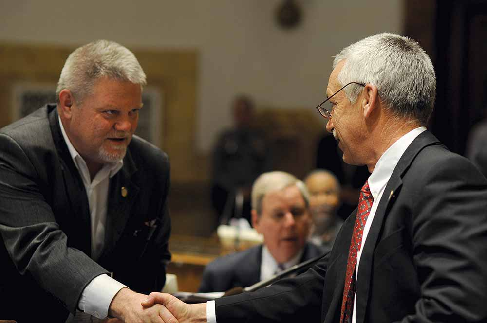 Sen. Perry Clark, D-Louisville, left, congratulates Sen. Paul Hornback, R-Shelbyville, following passage of the somewhat controversial industrial hemp bill in the Kentucky Senate. Hornback sponsored the legislation, which passed both chambers with an amendment on the last day of the General Assembly session. The bill creates an administrative framework for farmers to grow industrial hemp in Kentucky if the federal government lifts restrictions against production. (Photo courtesy of LRC Public Information)