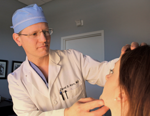 Plastic surgeon Dr. David Kirn examines a patient in his Lexington office.