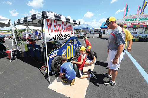 Kids practice being pit crew members at Kentucky Speedway.