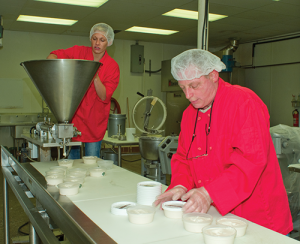 Lewis Shuckman, foreground, and his daughter Lauren package a variety of Shuckman's dips by hand. The Shuckman family has developed a nationally known product in their small value-added agriculture processing facility in downtown Louisville.
