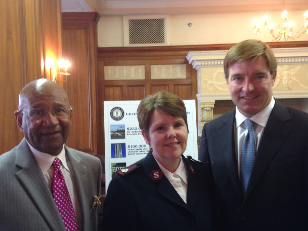 P.G. Peeples of the Urban League, left, and Major Debra Ashcraft of the Salvation Army of Central Kentucky, and Attorney General Jack Conway celebrate the announcement of $750,000 in funds to help displaced Lexington families.
