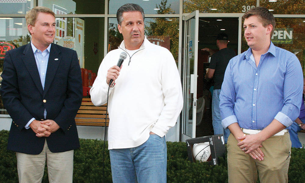 University of Kentucky men's basketball coach John Calipari, center, speaks to the crowd at Orange Leaf Frozen Yogurt Shop as Agriculture Commissioner James Comer, left, and Evan Morris, co-owner of Orange Leaf, listen in Tuesday in Lexington. (Kentucky Department of Agriculture photo)