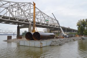 Twelve-foot diameter casings lay on the causeway ready to form the underwater support for the Downtown Crossing's piers.