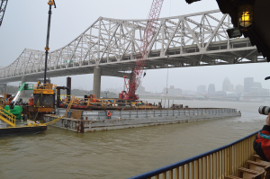 A barge full of equipment being used to construct Tower 5 is shown next to Kennedy Bridge in Louisville.