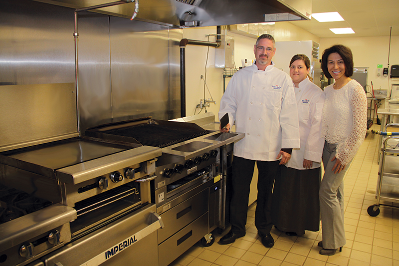 New menu items take six months to emerge publicly from Long John Silver's test kitchen, where up to 10 products can be in five-step innovation process, focused now on healthier offerings. Standing next to the test kitchen grill are, from left, Kevin Ash, product development chef; April Thompson food innovation fit coordinator; and Maria Zhang, chief food innovation officer for Long John Silver's.
