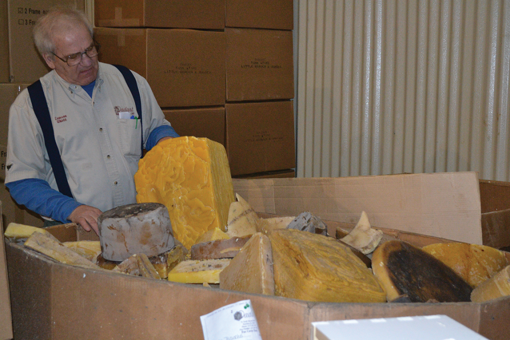 Clay Guthrie of beekeeping supplier Dadant & Sons in Frankfort inspects blocks of beeswax, which he will ship to western Illinois for candle production. (Photo by Kristi L. Branham)