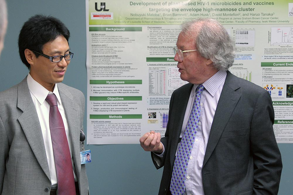 John Codey (right) of the Helmsley Charitable Trust discusses with Dr. Nobuyuki Matoba his work into finding a vaccine to prevent cholera, which in turn would prevent some cases of colon cancer. Dr. Matoba's work is one of the projects being supported by a $5.5 million grant from the Helmsley Charitable Trust.
