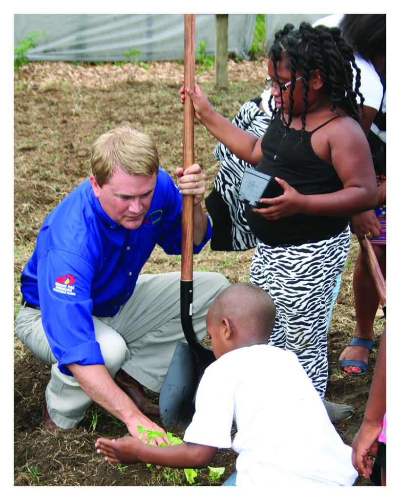 Agriculture Commissioner James Comer helps two members of the Parkland Boys and Girls Club start their garden following the ceremony to launch the Seed to Sale program July 2 in Louisville.