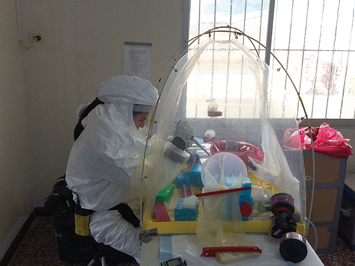 U.S. Navy personnel work in protective equipment while testing patient samples for the presence of the Ebola virus.