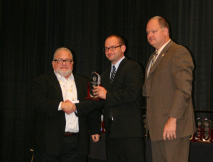 From left, Steve Lasky, Secured Cities Conference director, presents UK Police Major Nathan Brown and UK Police Chief Joe Monroe with the Security Innovation Award. Photo courtesy UK Police.