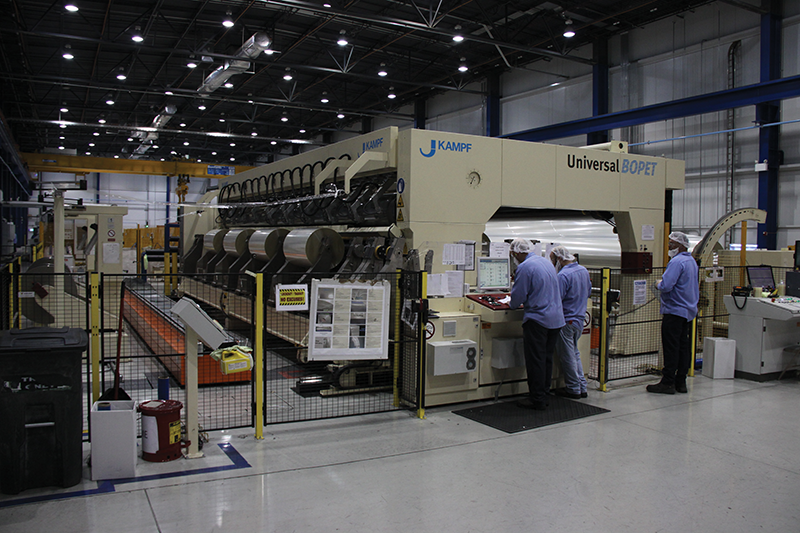 Workers at the $130 million Flex Films USA manufacturing plant in Elizabethtown prepare equipment to apply finishing processes to plastic film that will become product packaging. The Indian owned company expects work to add a second production line to begin some time in 2015.