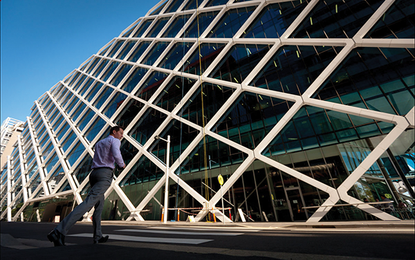 A pedestrian crosses the road in front of the Macquarie Group Building in Sydney, Australia. Macquarie Group Ltd. had surplus capital of A$3.4 billion.