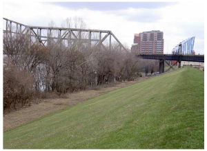 Part of the proposed Covington Riverfront Commons trail, heading east along the flood wall, with the new Ascent at the Roebling Bridge on the right in the background.