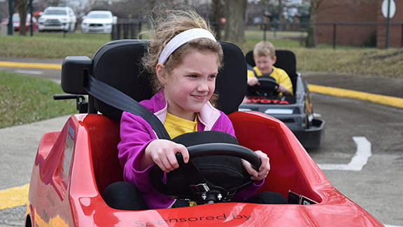 Second grader McKenzie Hutchinson transforms from pint-sized passenger to determined driver as she maneuvers through an intersection at Safety City in Lexington, Ky.