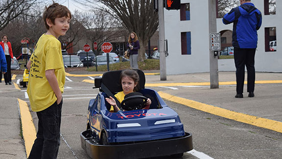 Driver Brooklyn Walls demonstrates the right of way the right way, stopping at a stop sign to let pedestrian Christian Newman cross the street at Safety City in Lexington, Ky.