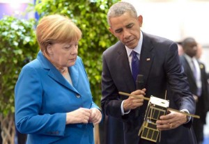 German Chancellor Angela Merkel and President Obama examine a Kentucky Space created CubeSat at the Hanover Messe industrial fair Monday in Germany.