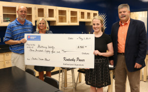 Hazard High School Principal Happy Mobelini and Assistant Superintendent Sondra Combs joined Kentucky Power's Greg Sparkman as he presents teacher Brittany Wolfe with a Teacher Vision Grant to buy supplies for the school's new lab.