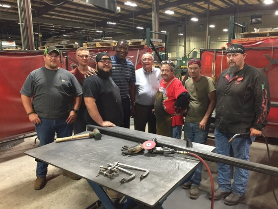Workers with Phillips Diversified Manufacturing stood with Labor Secretary Derrick Ramsey.