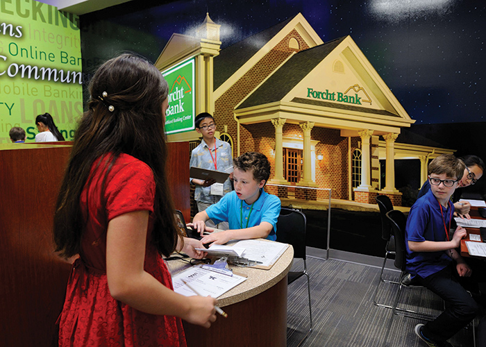 After preparing in their classrooms for a day in the simulated town, Biz Town students get to work soon after arriving at Junior Achievement of the Bluegrass.