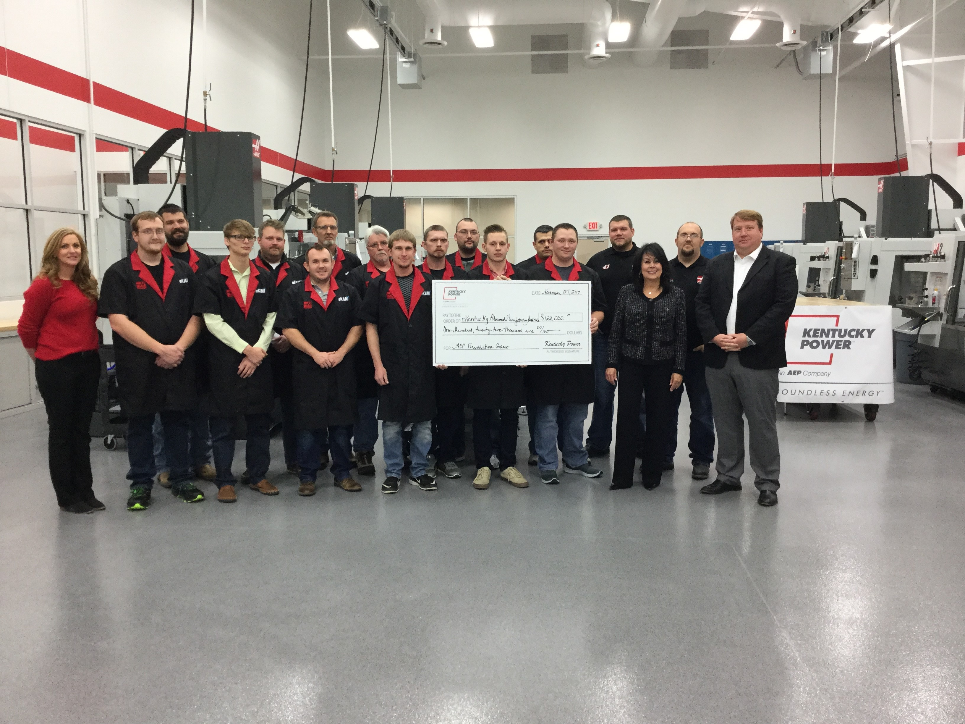 Kentucky Power President Matt Satterwhite, right, presents an AEP Foundation grant of $122,000 to Kathy Walker, second from right, for the eKentucky Advanced Manufacturing Institute. They are joined by students on their first day of classes at the new training facility in Paintsville.
