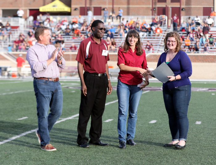 Caci Gibson, far right, accepts EKU's first Photon Fellowship at the recent Homecoming game.