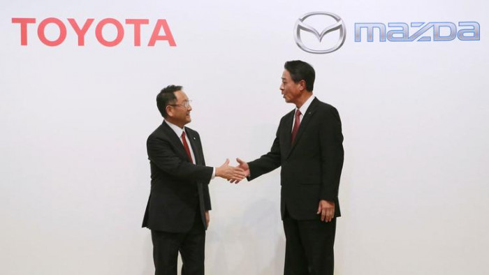 Toyota President Akio Toyoda, left, and Mazda President Masamichi Kogai shake hands in August 2017. (Eugene Hoshiko / Associated Press)