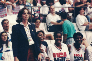Dr. Ireland stands to the left of the screen with 3 members of the U.S. women's basketball team sitting to her right.