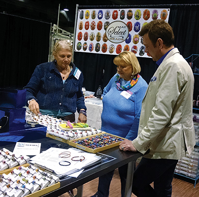Kentucky Artisan Center at Berea Executive Director Todd Finley examines artwork at the  2017 Kentucky Crafted Market. Kentucky Crafted artists make up about 40 percent of the artists whose work is sold at the Artisan Center.